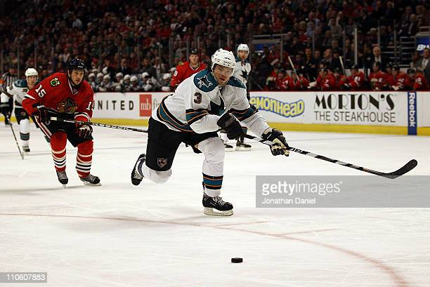 Douglas Murray of the San Jose Sharks chases down the puck in front of Fernando Pisani of the Chicago Blackhawks at the United Center on March 14...