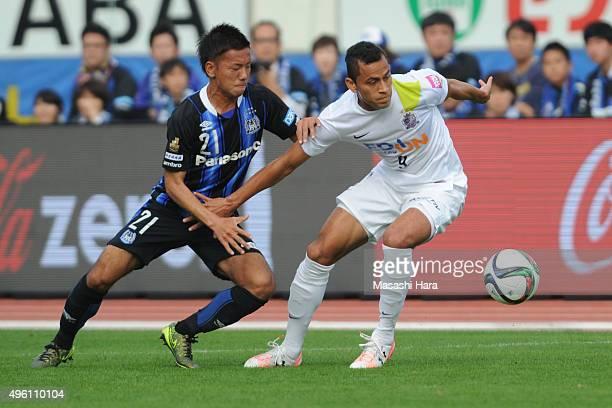 Douglas of Sanfrecce Hiroshima and Yosuke Ideguchi of Gamba Osaka compete for the ball during the JLeague match between Gamba Osaka and Sanfrecce...