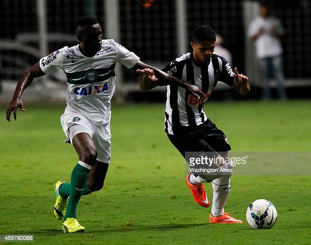 Douglas Santos of Atletico MG struggles for the ball with Joel Tadjo of Coritiba during a match between Atletico MG and Coritiba as part of...