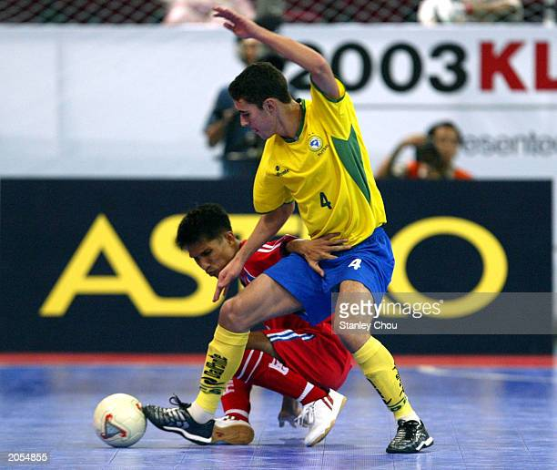 Dovenir Dominigues Neto of Brazil is held off by Anucha Manjarern of Thailand during the match between Thailand and Brazil in the 2003 World 5's...