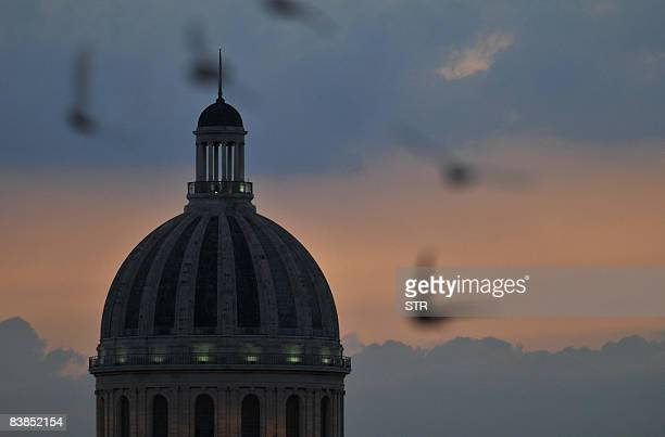 Doves fly around the dome of the Cuban Capitol in Old Havana at sunset on November 28 2008 AFP PHOTO/STR