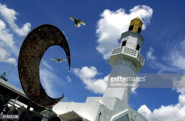 Doves fly over the crescent moon the symbol of Islam at the Kaumpurnah mosque in Basilan island while residents attend Friday prayers 08 June 2001...