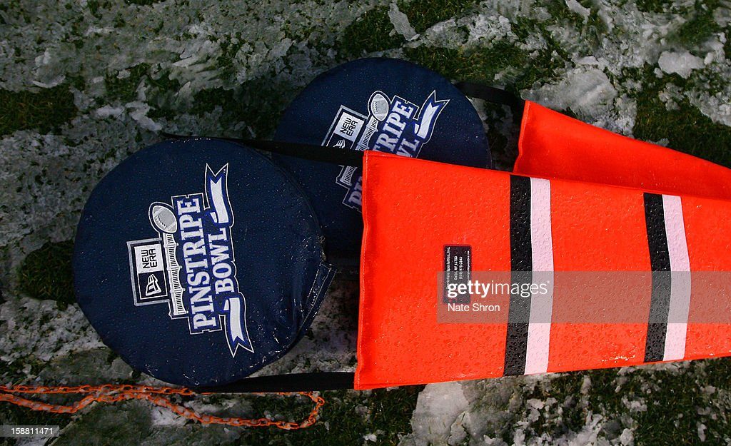 Down markers are seen laying on the field in snow with the New Era Pinstripe Bowl logo during the game between the Syracuse Orange and the West Virginia Mountaineers during the New Era Pinstripe Bowl at Yankee Stadium on December 29, 2012 in the Bronx borough of New York City.