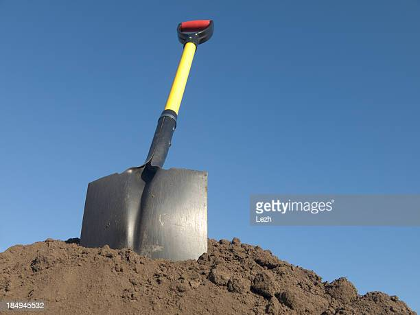 Down view of a shovel in a pile of soil