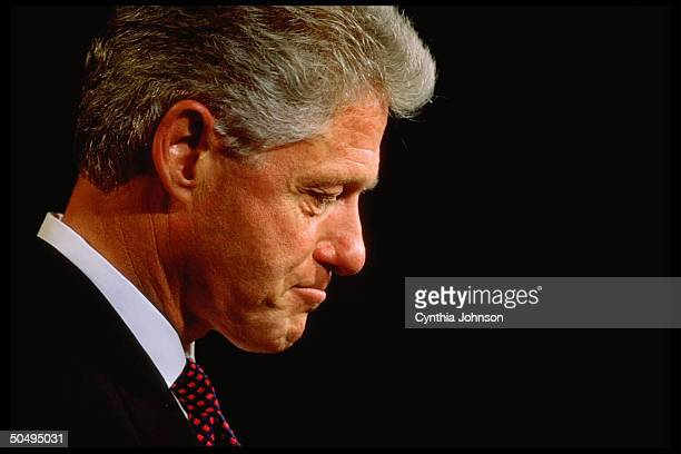Downcast Pres Bill Clinton in profile portrait appearing at Pine Crest Elementary School trying to maintain normal duties of presidency despite...