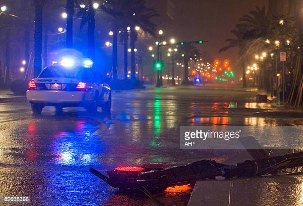 A downed traffic light still flickers as a New Orleans Police Department car patrols Canal Street at the intersection with LaSalle St in downtown New...
