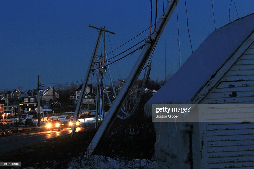 Downed utility poles and wires line the road near Bert's restaurant on Plymouth Beach on Sunday, Feb. 10, 2013, after a blizzard hit New England.