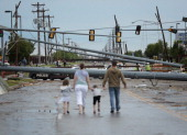 Downed utility poles block the road as a family walks south on Sante Fe Avenue at SW 19th Street after yesterday's deadly tornado on May 21 2013 in...
