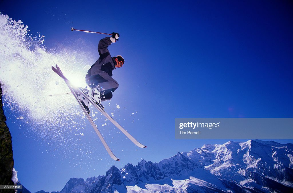 Downhill skier jumping, side view, low angle view : Stock Photo