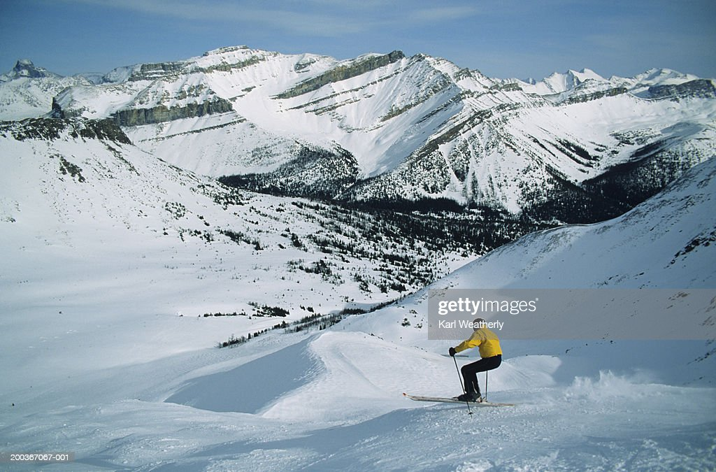 Downhill skier, mountains in background, Lake Louise, Alberta, Canada