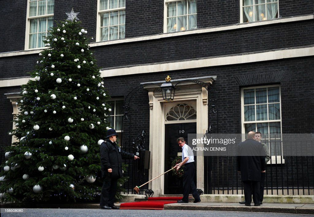 A Downing Street employee sweeps the red carpet beside a police officer ahead of a visit by Britain's Queen Elizabeth II outside No 10 Downing Street in London December 18, 2012. Queen Elizabeth II attended her first-ever cabinet meeting on Tuesday to mark her diamond jubilee, the only monarch to do so since 1781.The 86-year-old sovereign sat in as an observer on the meeting and received a gift from the Cabinet to celebrate her 60 years on the throne.
