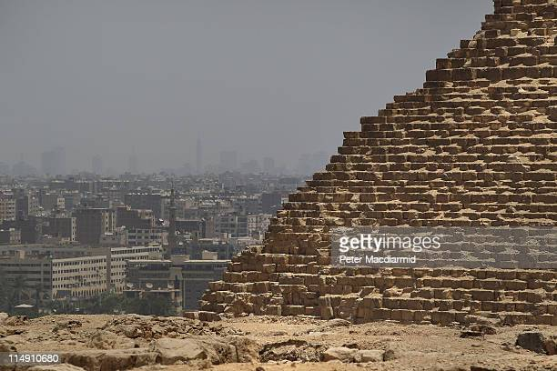 Downtown Cairo is visible behind the Great Pyramid of Cheops on May 28 2011 in Giza Egypt Protests in January and February brought an end to 30 years...