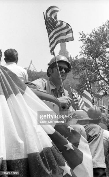 A construction worker sits with an American Flag in hand along side his fellow construction workers and war veterans alike to protest Mayor Lindsey's...