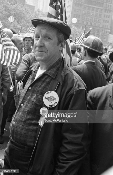 A older man stands proudly with construction workers and war veterans with an 'I Love America' pin prominently displayed and protests Mayor Lindsey's...