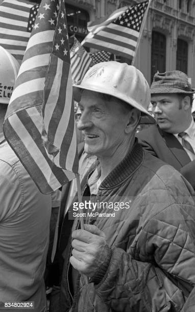 An older war veteran stands with an American Flag in hand and protests along side construction workers and other veterans alike Mayor Lindsey's...