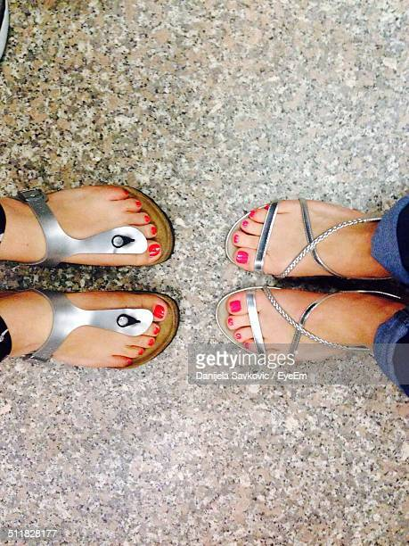 Downward view of sandals and feet of two women facing each other