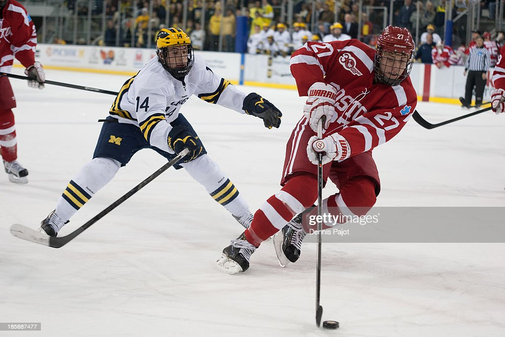 Doyle Somerby #27 of the Boston University Terriers skates against Tyler Motte #14 of the Michigan Wolverines on October 25, 2013 at Yost Ice Arena in Ann Arbor, Michigan.