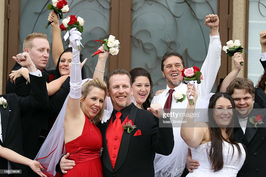 A dozen newlyweds pose for photos after participating in a mass wedding as part of a radio station contest at the Little Chapel of the Flowers on December 12, 2012 in Las Vegas, Nevada. Couples around the world are hoping that a once-in-a-lifetime event, the date 12/12/12, will bring added luck to their marriages if they tie the knot today. This will be the last such triple date for almost a century, until January 1, 2101.