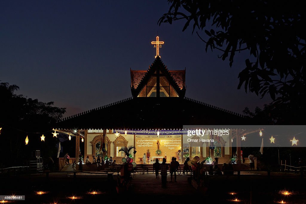 Dozens of Catholics gather at the church of Tahen Village to celebrate Christmas Eve on December 24, 2013 in Battambang, Cambodia. The parish at Battambang dates back to 1790 when the Catholic community first arrived. Now they serve around 1000 Catholics and 600 families.