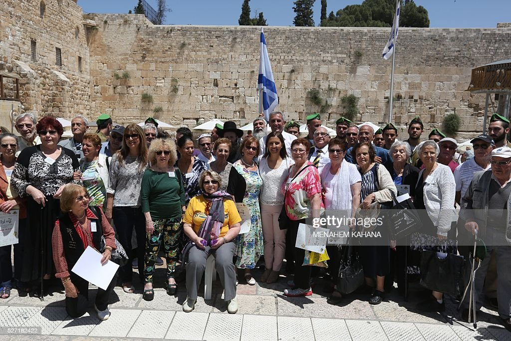 Dozens of Jewish holocaust survivors pose for a photo after performing their Bar-Mitzvah Jewish ceremony, normally done at the age of 13-years-old, on May 2, 2016, at the Western Wall in the Jerusalem's Old City. Some 50 male and female holocaust survivors were invited to perform the Jewish Bar-Mitzvah ceremony some 70 years after World War II. / AFP / MENAHEM