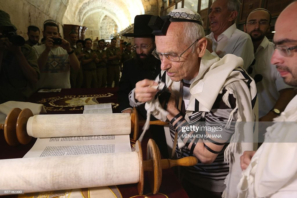 Dozens of Jewish holocaust survivors wear the Tefilin or the Phylacteries and the Tallit prayer shawl as they read from the Torah scrolls during their Bar-Mitzvah Jewish ceremony, normally done at the age of 13-years-old, on May 2, 2016, at the Western Wall in the Jerusalem's Old City. Some 50 male and female holocaust survivors were invited to perform the Jewish Bar-Mitzvah ceremony some 70 years after World War II. / AFP / MENAHEM