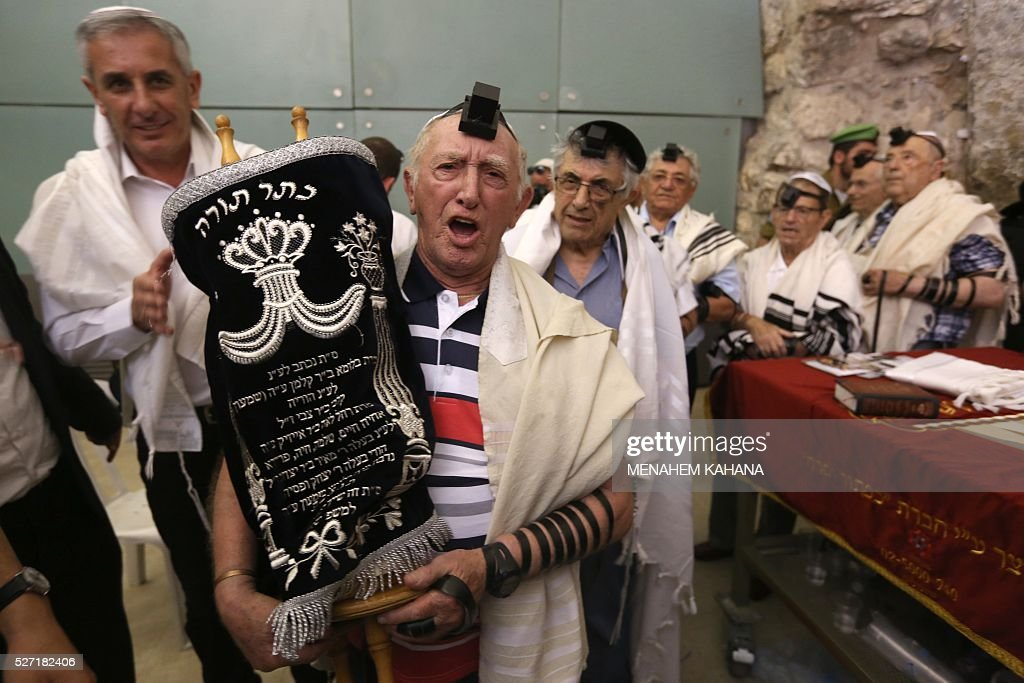 Dozens of Jewish holocaust survivors wear the Tefilin or the Phylacteries and the Tallit prayer shawl as they dance with the Torah after performing their Bar-Mitzvah Jewish ceremony, normally done at the age of 13-years-old, on May 2, 2016, at the Western Wall in the Jerusalem's Old City. Some 50 male and female holocaust survivors were invited to perform the Jewish Bar-Mitzvah ceremony some 70 years after World War II. / AFP / MENAHEM