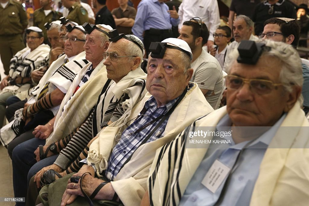 Dozens of Jewish holocaust survivors wear the Tefilin or the Phylacteries and the Tallit prayer shawl as they attend a Bar-Mitzvah Jewish ceremony, normally done at the age of 13-years-old, on May 2, 2016, at the Western Wall in the Jerusalem's Old City. Some 50 male and female holocaust survivors were invited to perform the Jewish Bar-Mitzvah ceremony some 70 years after World War II. / AFP / MENAHEM