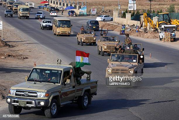 Dozens of Kurdish peshmerga fighters drive through Arbil after leaving a base in northern Iraq on October 28 2014 on their way to the battleground...