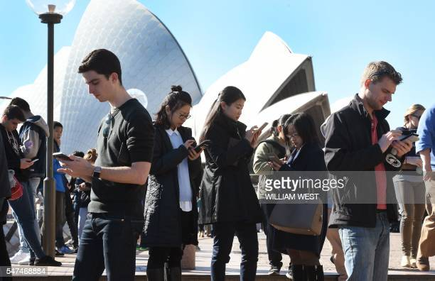 TOPSHOT Dozens of people gather to play Pokemon Go in front of the Sydney Opera House on July 15 2016 The wildly popular mobile app which is based on...