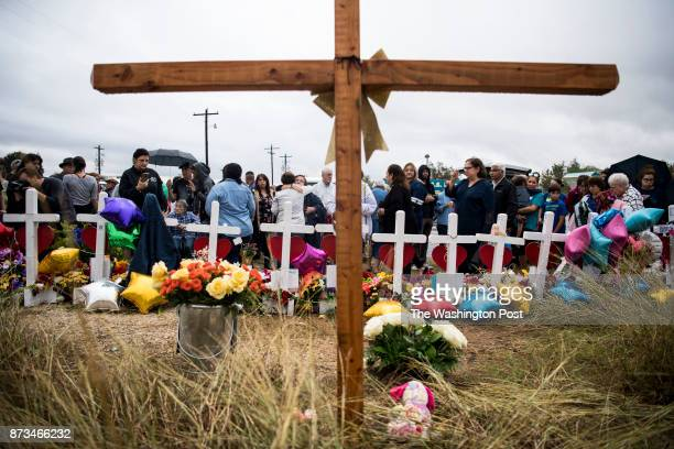 Dozens of people stand in the rain to pray and sing together at the memorial crosses near the Sutherland Springs First Baptist Church one week after...