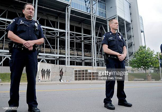 Dozens of police officers line Porter Road in front of the Joe Paterno statue as crews start to remove it shortly after 6 am on Sunday July 22 in...