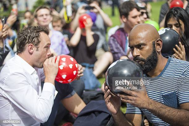 Dozens of protesters stage a mass inhalation of Nitrous Oxide commonly known as laughing gas outside the Houses of Parliament in central London on...