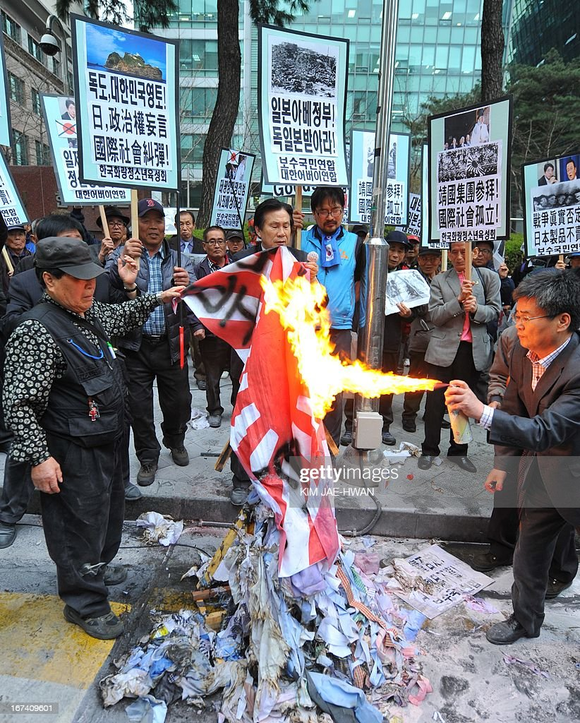 Dozens of South Korean activists burn a Japanese imperial army flag during a rally outside the Japanese embassy in Seoul on April 25, 2013. The rally came amid escalating diplomatic tensions over trips by Japanese officials and legislators to the controversial Yasukuni shrine in Tokyo.