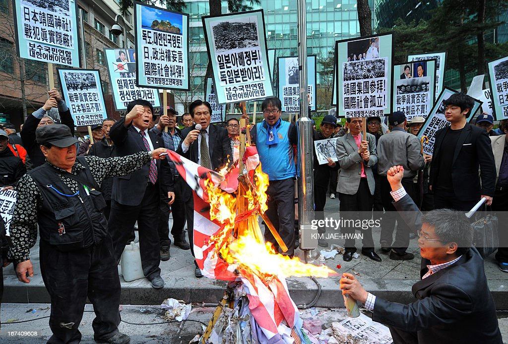 Dozens of South Korean activists burn a Japanese imperial army flag during a rally outside the Japanese embassy in Seoul on April 25, 2013. The rally came amid escalating diplomatic tensions over trips by Japanese officials and legislators to the controversial Yasukuni shrine in Tokyo. AFP PHOTO / KIM JAE-HWAN