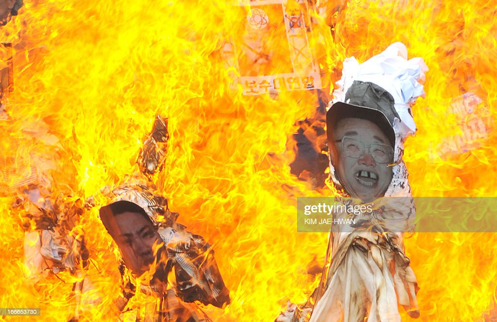 Dozens of South Korean activists burn effigies with the portraits of North Korea's late leader Kim Jong-Il (R) and his son and current leader Kim Jong-Un (L) during an anti-Pyongyang rally in Seoul on April 15, 2013, to mark the 101st birthday of the North's founder and late president Kim Il-Sung . Meanwhile South Korea voiced regret on April 15 at North Korea's dismissal of its offer for dialogue, as the South's armed forces remained on heightened alert for an expected missile test by Pyongyang. AFP PHOTO / KIM JAE-HWAN