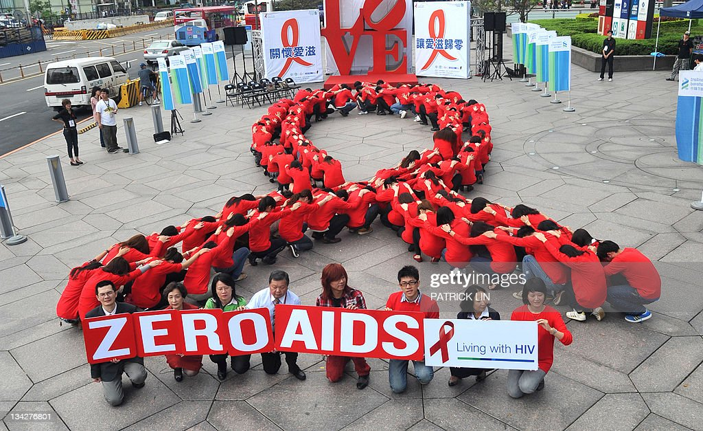 Dozens of volunteers join a human chain in the form of a red ribbon a symbol of 'love and care' for HIV and AIDS carriers worldwide at a gathering in...