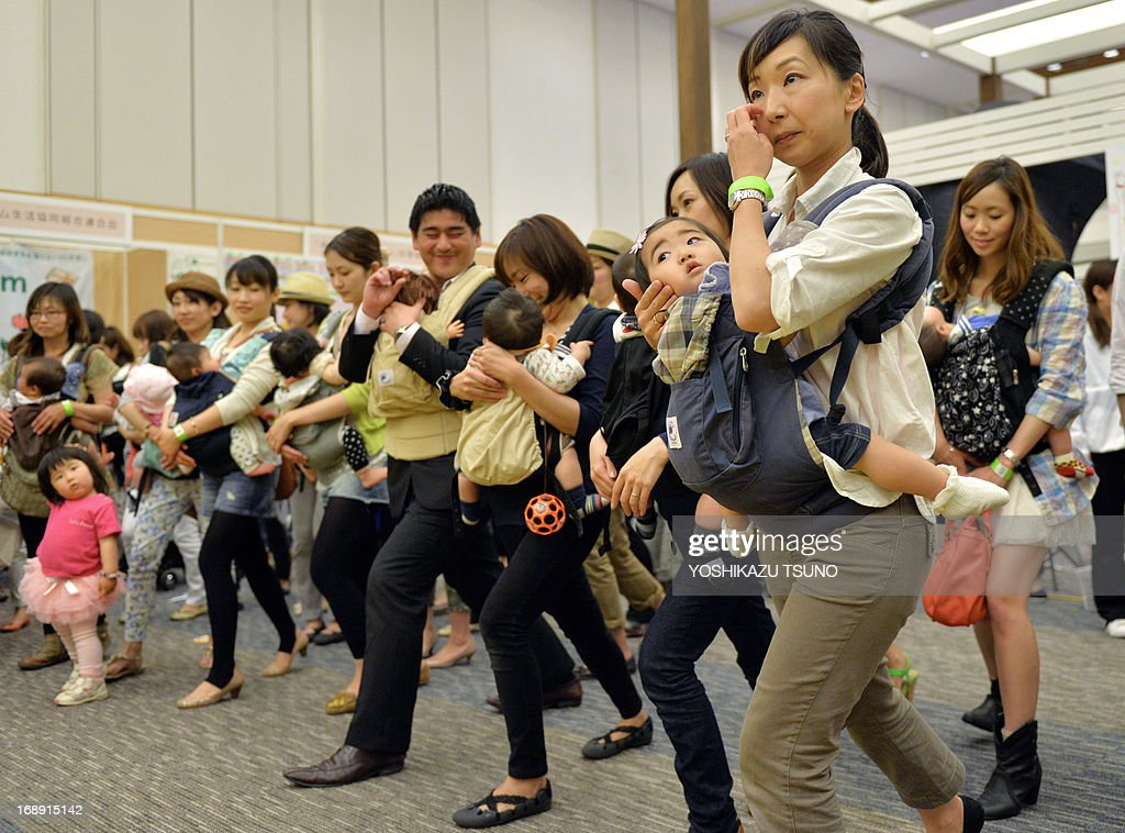 Dozens of young mothers samba dance with their babies at the Mama Fes event in Tokyo on May 17, 2013. Some 50,000 parents and their babies are expeting to visit a two-day event for workshops and talk-shows. AFP PHOTO / Yoshikazu TSUNO