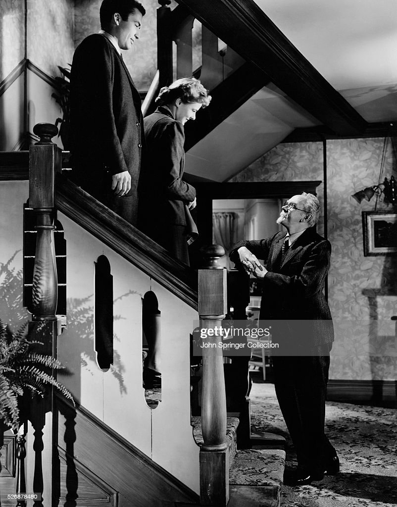 Dr. Alex Brulov (Michael Chekhov) waits for Dr. Constance Peterson (Ingrid Bergman) and John Ballantine (Gregory Peck) at the base of the stairs in a scene from Alfred Hitchcock's film Spellbound.