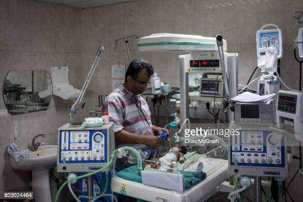 Dr Allam Abu Hamda tends to a a newborn baby suffering complications in the neonatal unit at Shifa hospital on July 19 2017 in Gaza City Gaza In the...