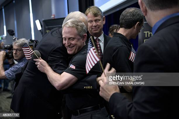 Dr Allan Stern principal investigator for NASA's New Horizons mission gets a hug while others celebrate the closest flyby of Pluto by the New...