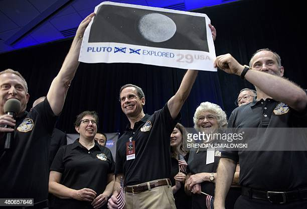 Dr Allan Stern principal investigator for the New Horizons mission to Pluto and others hold up their suggestion for a modified US Post Office stamp...