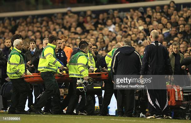Dr Andrew Deaner walks off the pitch as Fabrice Muamba of Bolton Wanderers is taken off on a stretcher still unconscious after receiving CPR...