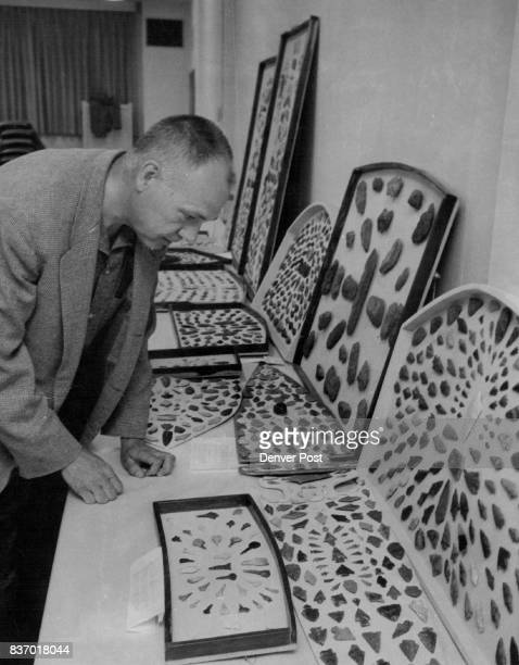 Dr Arthur Schoondermark of Fort Collins Colo examines a collection of arrowheads displayed by A R Hunter of Ada Okla at the 23rd annual Loveland...