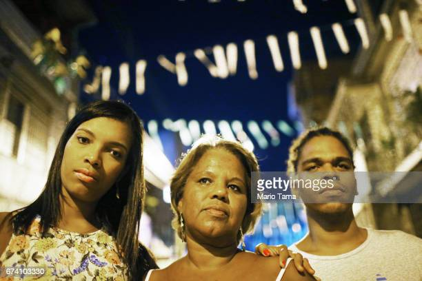 Dr êcaro Vidal dos Santos poses with sister Isis Carine Vidal dos Santos and mother Raimunda Vidal dos Santos outside his mother's home on April 18...