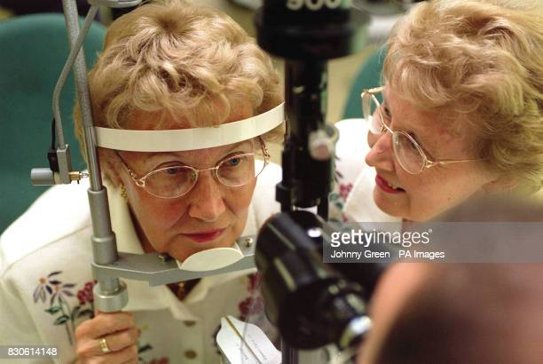 Dr Chris Hammond a consultant eyesurgeon examines the eyes of Rosemary Case as her twinsister Margaret Micklewright looks on at St Thomas' Hospital...