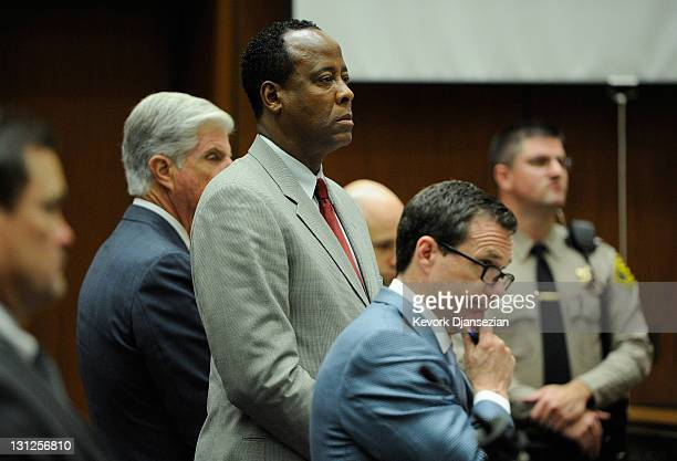 Dr Conrad Murray stands with defense attorney J Michael Flanagan and defense attorney Ed Chernoff prior to the start of morning's court proceedings...