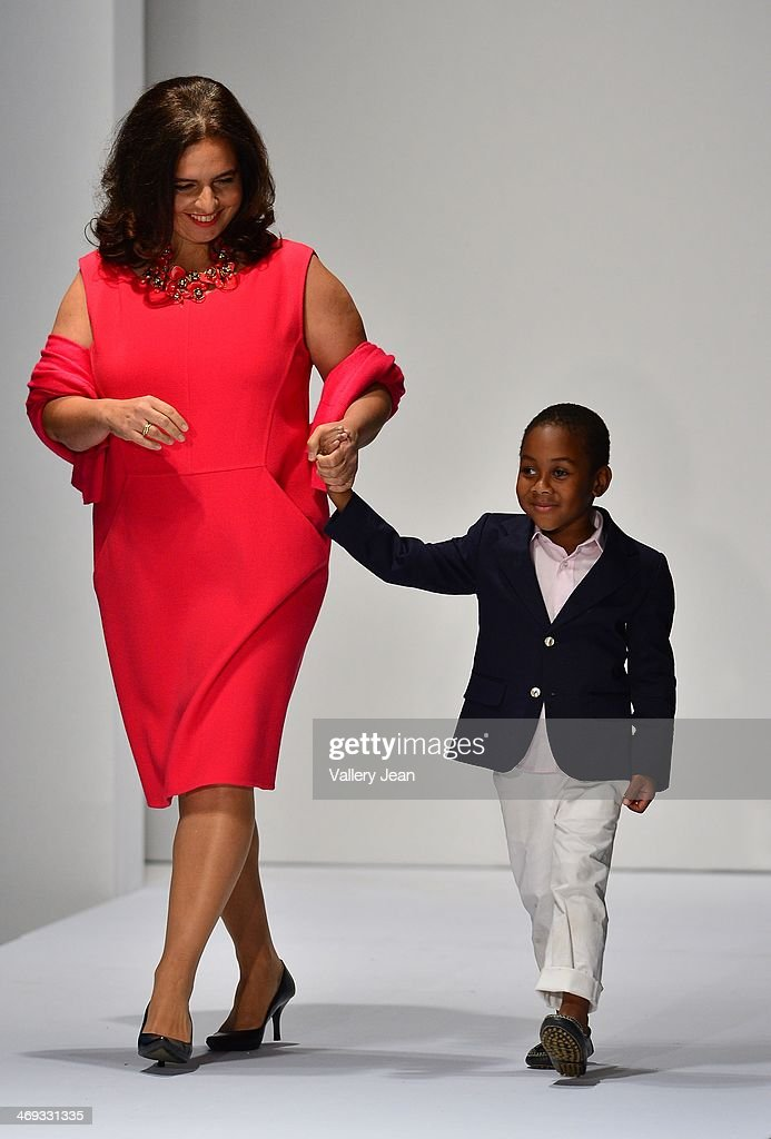 Dr. Cristina E. Fernandes and Brandon Johnson walk the runway during an Oscar de la Renta fashion show during the Designed For A Cure 2014 Benefiting Sylvester Comprehensive Cancer Center at Ice Palace on February 13, 2014 in Miami, Florida.
