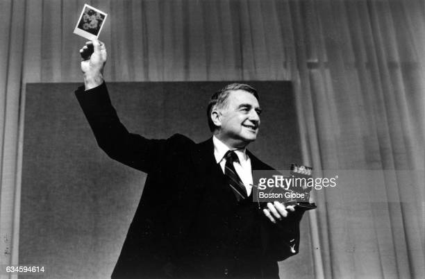 Dr Edwin H Land Chairman of the Board and Director of Research of Polaroid Corporation shows a print made with the company's new SX 70 color film...