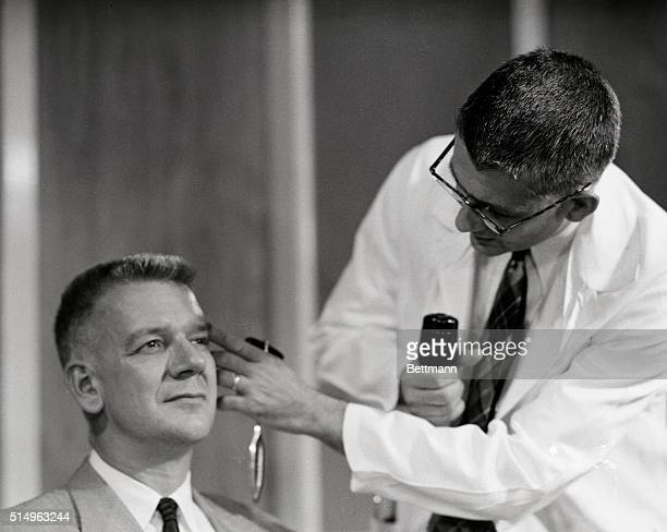 Dr Harry L Williams examines the eyes of Dr Carl Pfeiffer after administering LSD 25 the new drug which produces effects similar to those experienced...