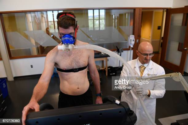 Dr Inigo San Millan right adjusts a breathing apparatus for triathlete Zach Barber before a metabolic and physiologic test in a lab at the University...